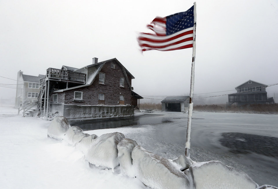 Photo - A tattered flag flies by a flooded yard along the shore in Scituate, Mass., Friday, Jan. 3, 2014. A blustering winter storm that dropped nearly 2 feet of snow just north of Boston, shut down major highways in New York and Pennsylvania and forced U.S. airlines to cancel thousands of flights nationwide menaced the Northeast on Friday with howling winds and frigid temperatures. (AP Photo/Michael Dwyer)