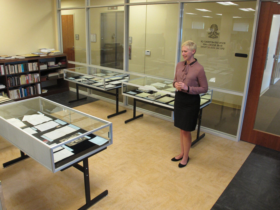 Photo - In this May 8, 2014 photo, University of South Carolina archivist Jessica Crouch looks over display cases of some of author Pat Conroy's papers at the university's library in Columbia, S.C. The university has obtained all of Conroy's handwritten manuscripts and other papers. (AP Photo/Jeffrey Collins)