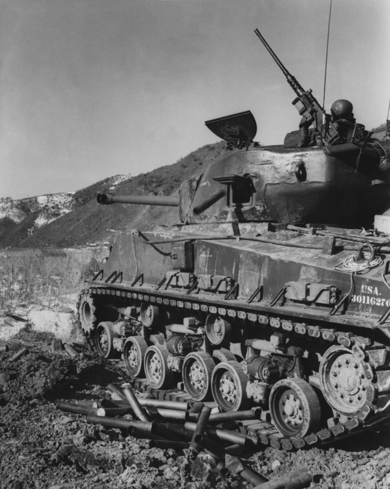 """Photo - With the U.S. 45th Infantry Division in Korea--A pile of empty 76 millimeter shell casings is witness to the misery this 45th Infantry division tank has been dealing  the enemy in Korea.  The tank was part of a patrol into enemy territory in a probing action.  The 45th 'Thunderbird' division, formerly the Oklahoma National Guard, has been in action in Korea since the first week of December, when units of the 'Fighting Forty-Fifth' started arriving from their training camps in Hokkaido, northernmost island of Japan.""""  U.S. Army Photo by Cpl. Eugene Turner.  Original undated.  Entered the library on 01/31/1952."""