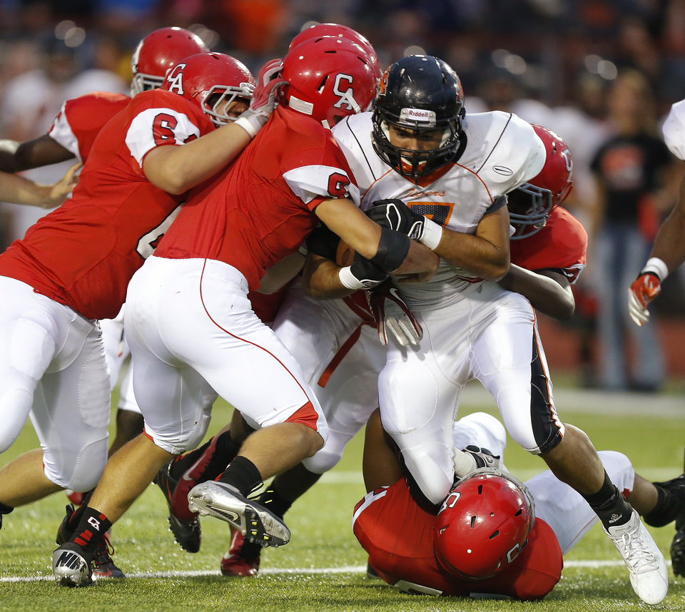 Photo - Coweta's Randall Smith is stopped by a gang of Carl Albert defenders during a high school football game at Carl Albert in Midwest City, Friday, September 7, 2012. Photo by Bryan Terry, The Oklahoman