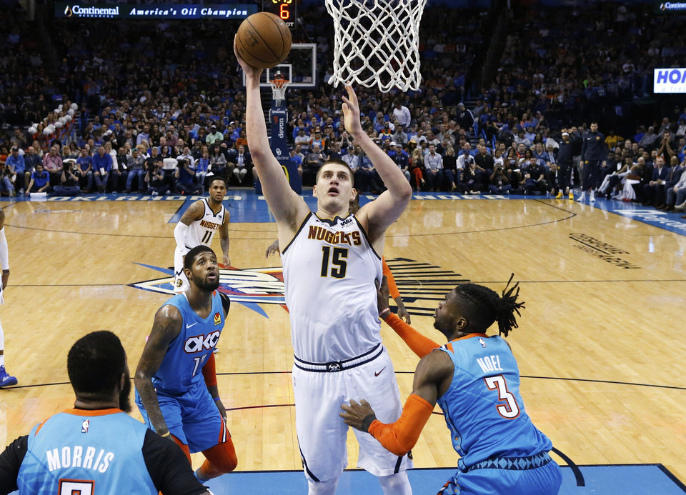 Photo - Denver Nuggets center Nikola Jokic (15) shoots between Oklahoma City Thunder forward Markieff Morris, left, forward Paul George, rear, and forward Nerlens Noel (3) during the second half of an NBA basketball game Friday, March 29, 2019, in Oklahoma City. (AP Photo/Sue Ogrocki)