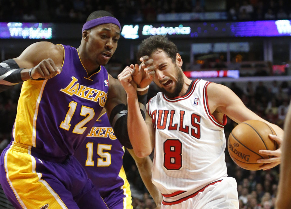 Photo - Los Angeles Lakers center Dwight Howard (12) fouls Chicago Bulls guard Marco Belinelli during the second half of an NBA basketball game Monday, Jan. 21, 2013, in Chicago. The Bulls won 95-83. (AP Photo/Charles Rex Arbogast)