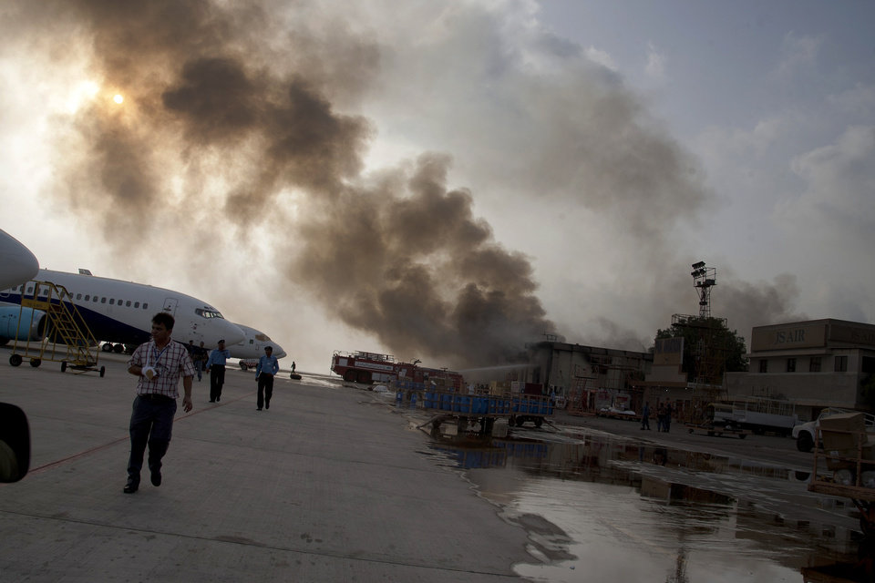 Photo - Smoke rises above the Jinnah International Airport where security forces continue to battle militants Monday, June 9, 2014, in Karachi, Pakistan. Gunmen disguised as police guards attacked a terminal with machine guns and a rocket launcher during a five-hour siege that killed 13 people as explosions echoed into the night, while security forces retaliated and killed all the attackers, officials said Monday. (AP Photo/Shakil Adil)