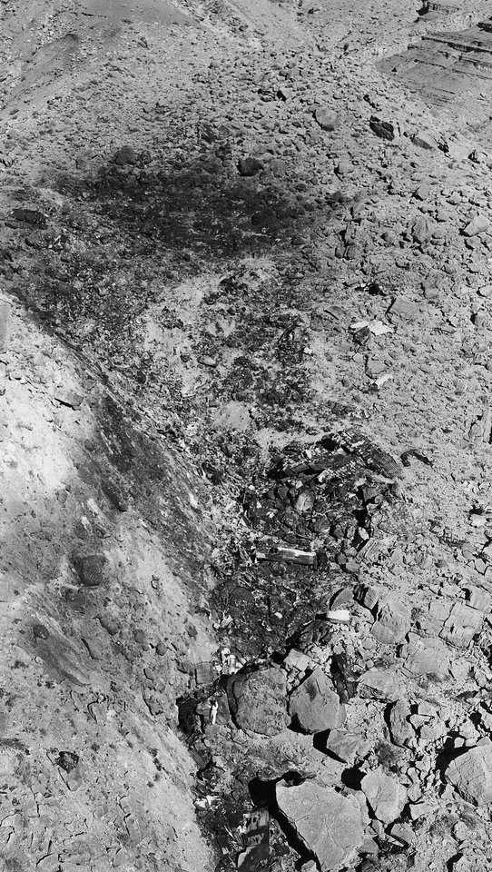Photo - FILE - This July 3, 1956 file photo, a man, lower center, stands near small pieces of wreckage from the crash of TWA Super-Constellation on June 30, 1956, killing 70 people. The burned spot is about 200 feet high and a 100 feet wide in Grand Canyon, Ariz.  The crash spurred improvements to the air traffic control and radar systems, and led to the creation of the Federal Aviation Administration. On Tuesday, July 8, 2014, the Grand Canyon National Park will mark the designation of the crash site as a National Historic Landmark in a ceremony overlooking the gorge where the wreckage was scattered over 1.5 square miles.  (AP Photo/David F. Smith, File)