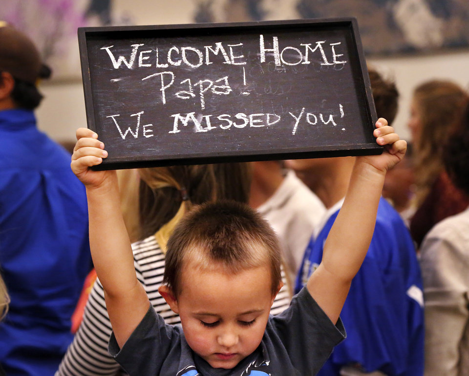 Photo - A small boy looks down from the chair he is standing on and holds a sign above his head welcoming home his grandfather following an extended tour of duty overseas. At least 1,000 people, mostly spouses, children, relatives and friends, crowded into a large room in the Armed Forces Reserve Center in Norman on Saturday, Sep. 28, 2013, to give a boisterous, and at times, tearful welcome  to members of the Oklahoma National Guard who returned to Norman after 10 months in Afghanistan. After a brief ceremony, which included a personal thank-you to his troops from Maj. Gen. Myles Deering, the soldiers were dismissed to an emotional reunion with their love ones. Deering serves as adjutant general of Oklahoma.  Photo  by Jim Beckel, The Oklahoman.