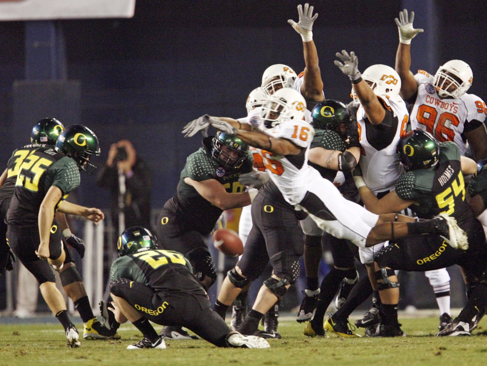 Photo - OSU's Perrish Cox (16) blocks a field goal attempt by Oregon's Morgan Flint (25) in the second quarter of the Holiday Bowl college football game between Oklahoma State and Oregon at Qualcomm Stadium in San Diego, Tuesday, Dec. 30, 2008. PHOTO BY NATE BILLINGS, THE OKLAHOMAN