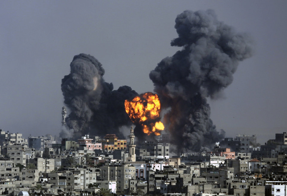 Photo - Smoke and fire from the explosion of an Israeli strike rise over Gaza City, Tuesday, July 22, 2014, as Israeli airstrikes pummeled a wide range of locations along the coastal area and diplomatic efforts intensified to end the two-week war. Disagreement over whether to lift the Gaza blockade is a key stumbling block to ending more than two weeks of fighting between the Islamic militant Hamas and Israel. Some in Gaza say they would rather endure more fighting than return to life under the blockade. (AP Photo/Hatem Moussa)