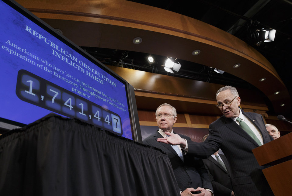 Photo - Sen. Charles Schumer, D-N.Y., the Democratic Policy Committee chairman, right, accompanied by Senate Majority Leader Harry Reid of Nev., points to a graphic during a news conference on Capitol Hill in Washington, Thursday, Feb. 6, 2014, where they told reporters that Republicans are thwarting Democratic efforts pass a bill to extend unemployment benefits which expired at the end of last year.  (AP Photo/J. Scott Applewhite)