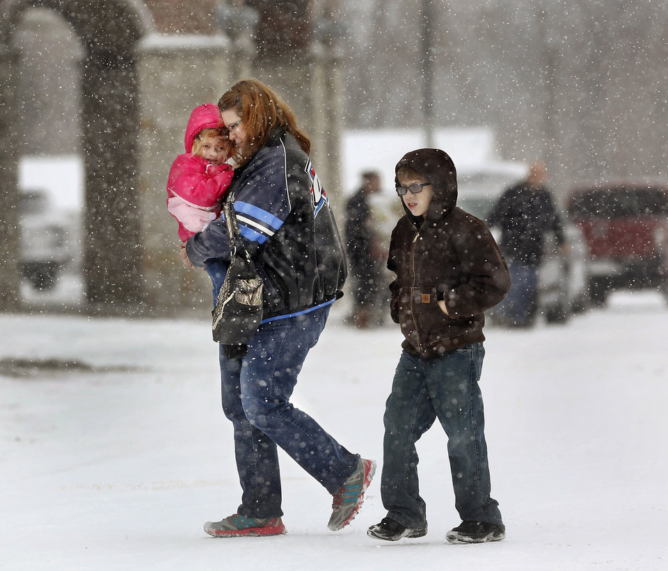Photo - A woman carries a child across a snow-covered parking lot at Crest Foods in Midwest City. Snow began falling in central Oklahoma around 7 Sunday morning, Feb. 2, 2014.   Photo by Jim Beckel, The Oklahoman