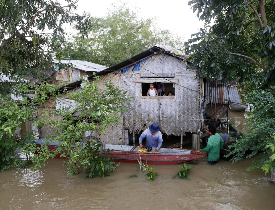 Photo - A resident repairs his boat outside of his flooded home from Typhoon Koppu, in La Paz township, Tarlac province, in northern Philippines Tuesday, Oct. 20, 2015. Slow-moving Typhoon Koppu blew ashore with fierce winds in the northeastern Philippines early Sunday, toppling trees and knocking out power and communications and forcing the evacuation of thousands of villagers. (AP Photo/Bullit Marquez)