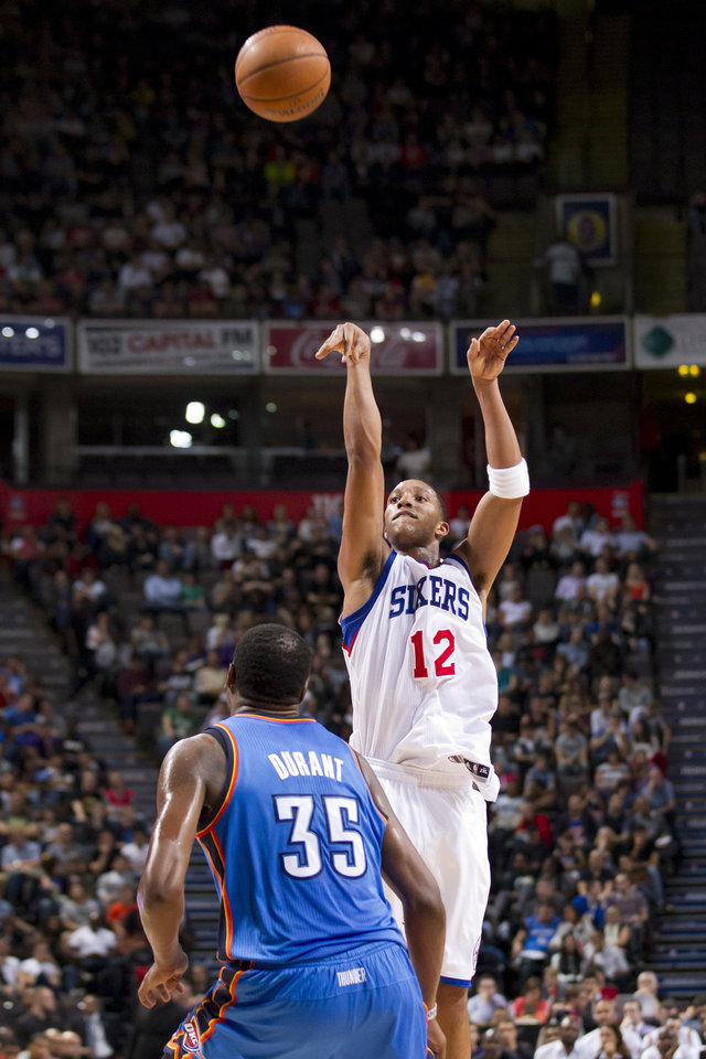 Photo - Philadelphia 76ers' Evan Turner, right, takes a shot as Oklahoma City Thunder's Kevin Durnat looks on during their NBA preseason basketball game at the Phones4 u Arena in Manchester, England, Tuesday, Oct. 8, 2013. (AP Photo/Jon Super) ORG XMIT: MJS104