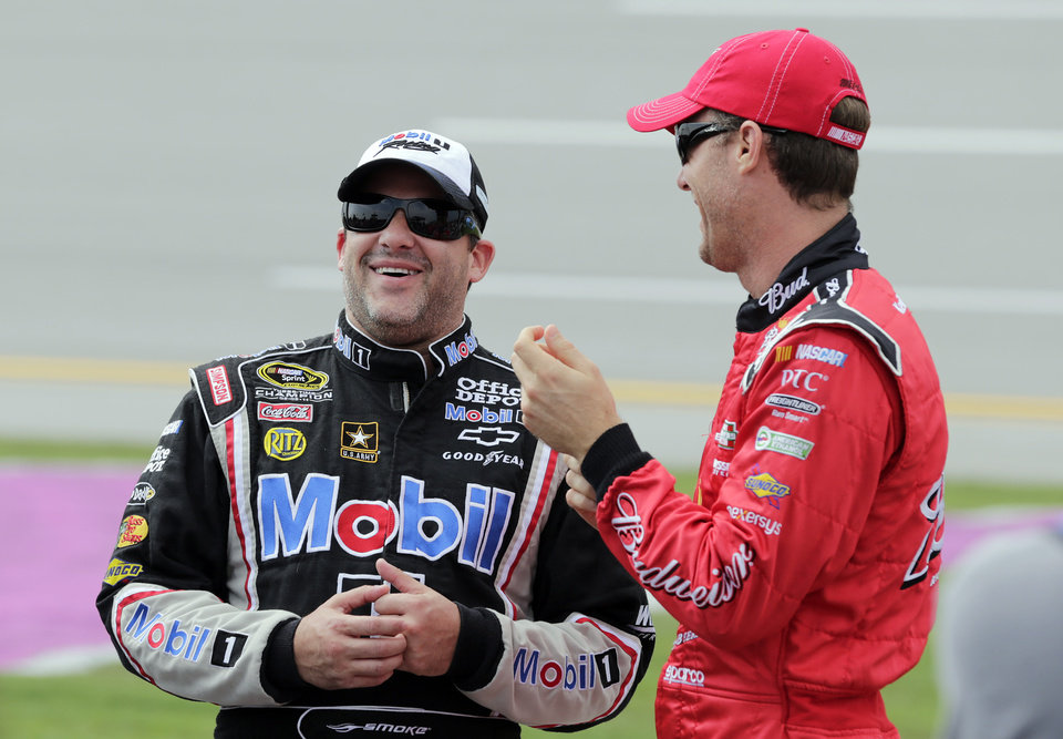 Photo -   NASCAR driver Tony Stewart, left, talks with Kevin Harvick prior to their qualifying runs at Talladega Superspeedway in Talladega, Ala., Saturday, Oct. 6, 2012. The drivers were qualifying for the Sunday running of the NASCAR Sprint Cup Series auto race. (AP Photo/Dave Martin)