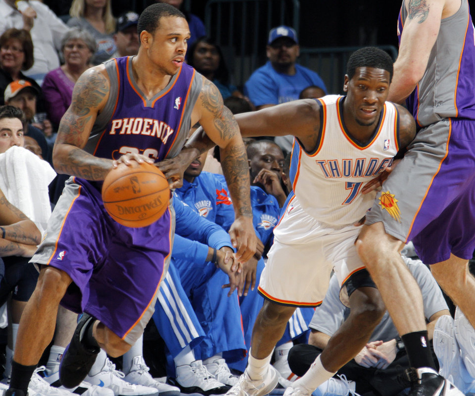 Photo - Oklahoma City Thunder point guard Royal Ivey (7) tries to stay with Phoenix Suns shooting guard Shannon Brown (26) during the NBA basketball game between the Oklahoma City Thunder and the Phoenix Suns at the Chesapeake Energy Arena on Wednesday, March 7, 2012 in Oklahoma City, Okla.  Photo by Chris Landsberger, The Oklahoman