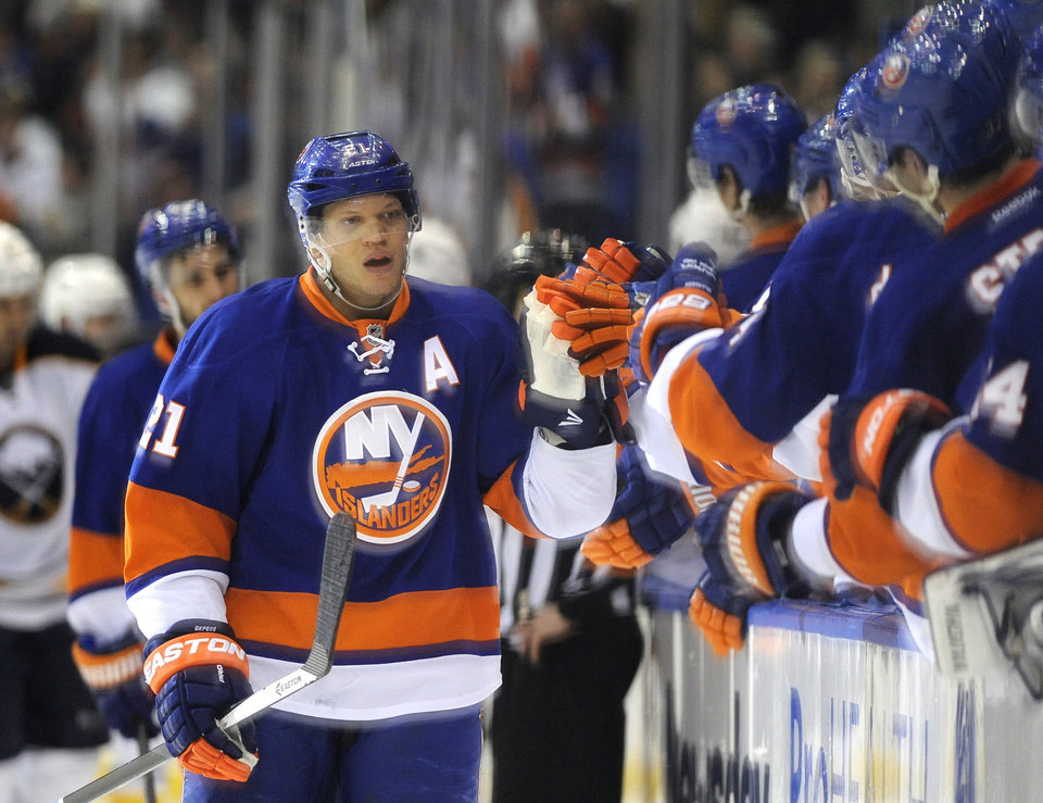 Photo - New York Islanders' Kyle Okposo (21) is congratulated by teammates after scoring against the Buffalo Sabres in the first period of an NHL hockey game on Saturday, March 15, 2014, in Uniondale, N.Y. (AP Photo/Kathy Kmonicek)