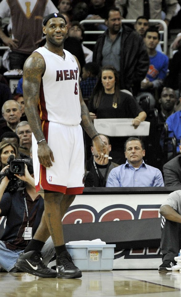 In this Dec. 2, 2010 file photo, Miami Heat forward LeBron James smiles as Cleveland Cavaliers owner Dan Gilbert, right, watches in the second quarter in Cleveland. (AP Photo/David Richard, File)