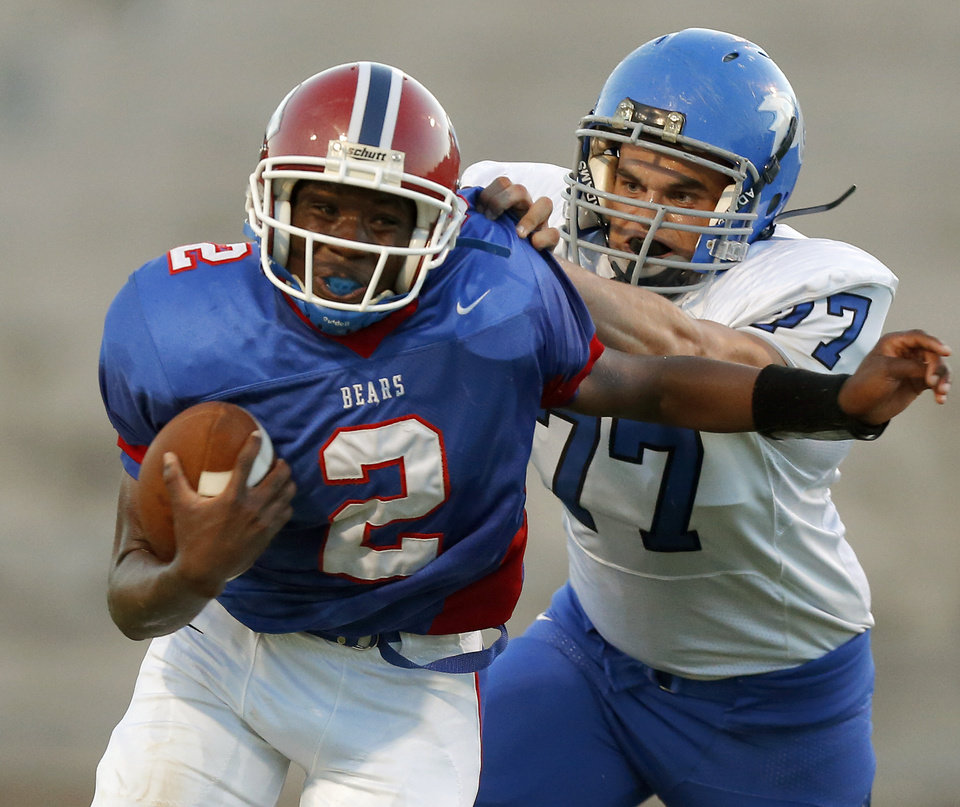John Marshall\'s Lenard Levinston fights off Bridge Creek\'s Shaine Coffman during a high school football game at Taft Stadium in Oklahoma City, Thursday, September 6, 2012. Photo by Bryan Terry, The Oklahoman