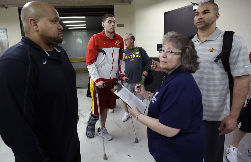 Photo - Iowa State's Georges Niang, center, checks in through security for the team's practice for the NCAA men's college basketball tournament, Saturday, March 22, 2014, in San Antonio. Niang broke his foot during a game Friday night and will not play when Iowa State faces North Carolina on Sunday. (AP Photo/Eric Gay)