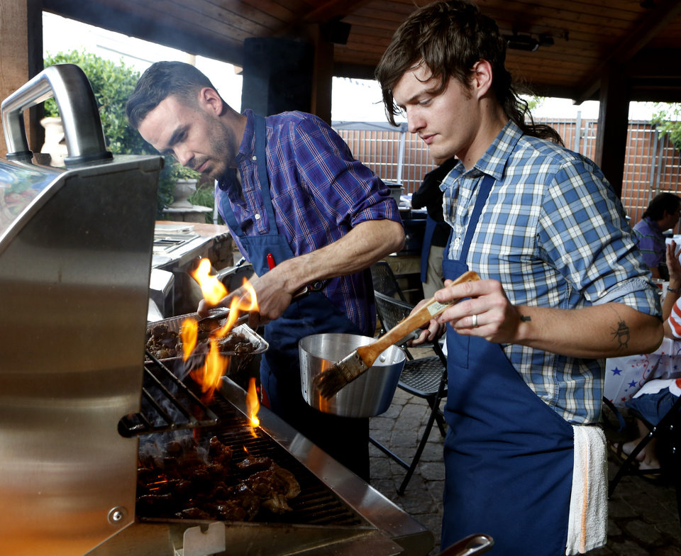 Photo - Open Flame guest chefs Colin Stringer and Andon Whitehorn prepare pork ribs on Thursday, June 12, 2014 in Oklahoma City, Okla.  Photo by Steve Sisney, The Oklahoman