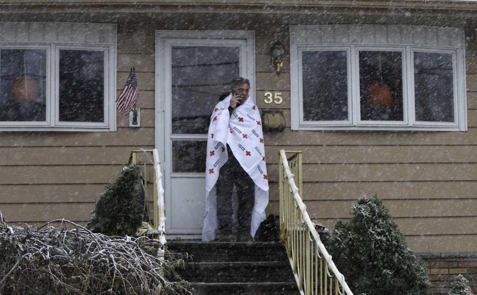 Ben Colontonio talks on his cell phone wrapped in a blanket donated by the American Red Cross as a Noreaster approached in the wake of Superstorm Sandy, Wednesday, Nov. 7, 2012, in Little Ferry, N.J. (AP Photo/Kathy Willens) ORG XMIT: NYKW105