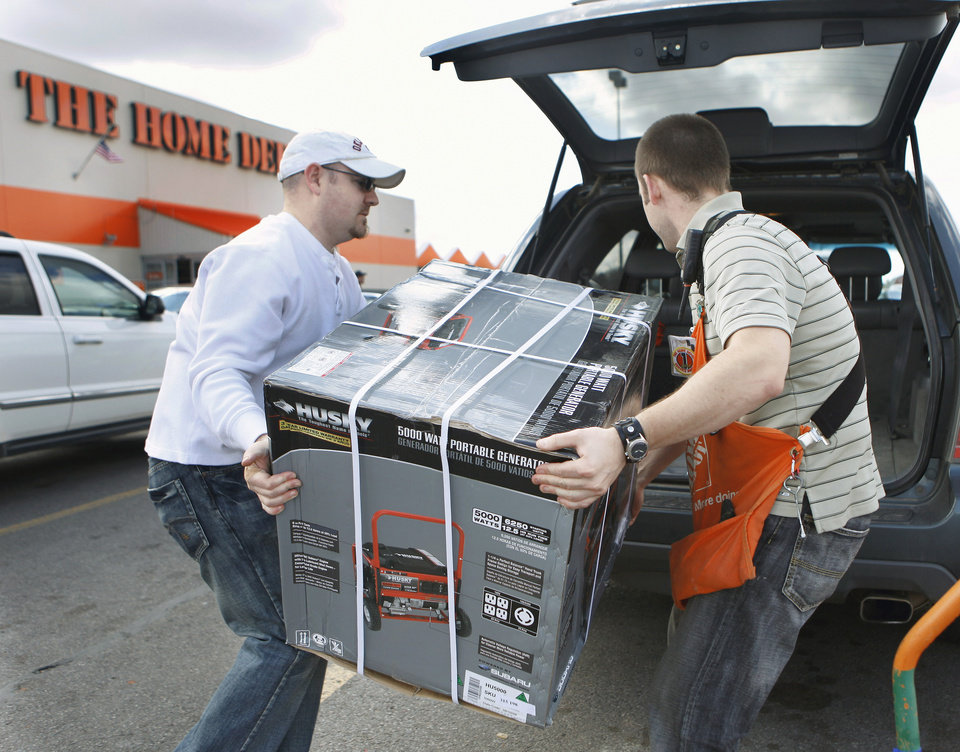 Photo - Terry Burton, of Piedmont, loads a generator with the help of Norman Home Depot employee Darren Parmele in preparation for an approaching winter storm Wednesday in Norman.  Photo by Steve Sisney, The Oklahoman