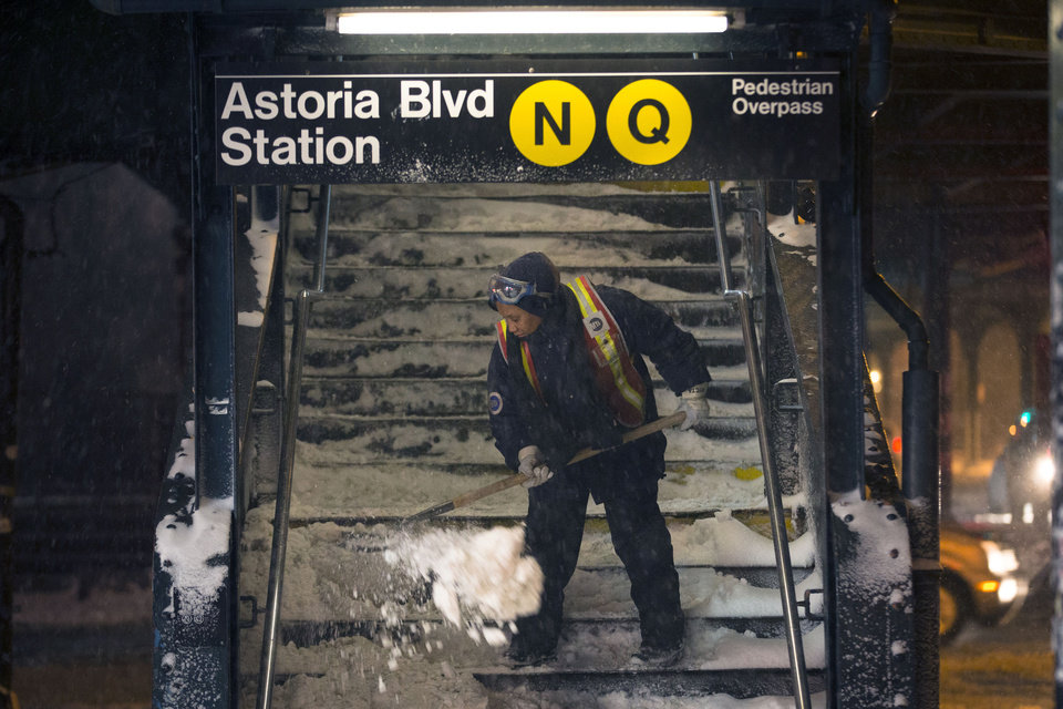 Photo - A worker clears snow from a stairway at the Astoria Blvd subway station, Friday, Jan. 3, 2014, in the Queens borough of New York. New York City public schools were closed Friday after up to 7 inches of snow fell by morning in the first snowstorm of the winter. (AP Photo/John Minchillo)