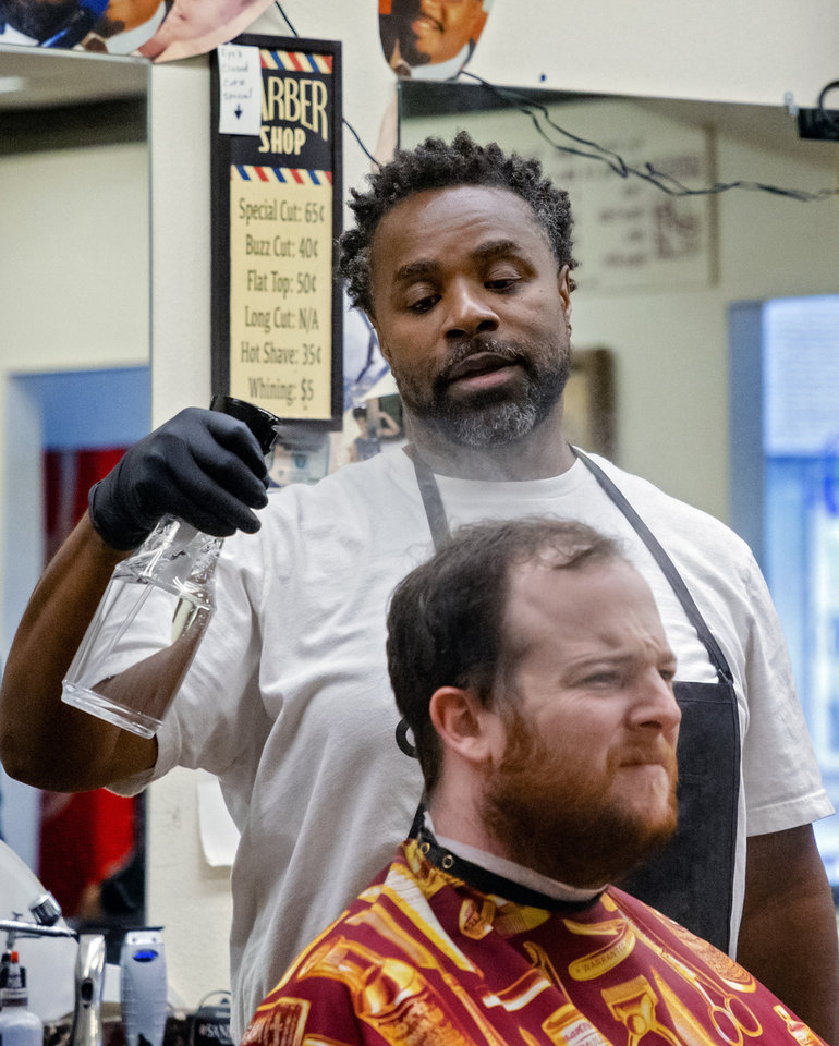 Photo - Barber Michael Mitchell prepares to cut the hair of The Oklahoma's David Dishman at Versatile Styles Barber Shop located at 9132 S. Walker Ave. on Tuesday, May 5, 2020, in Oklahoma City, Okla. . [Chris Landsberger/The Oklahoman]