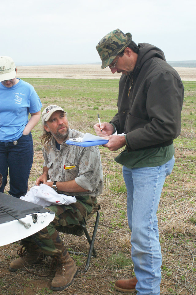 Photo - Biologist Don Wolfe, seated, takes measurements on a captured lesser prairie chicken as another biologist records data during a research field trip in Ellis County.  Photo Provided