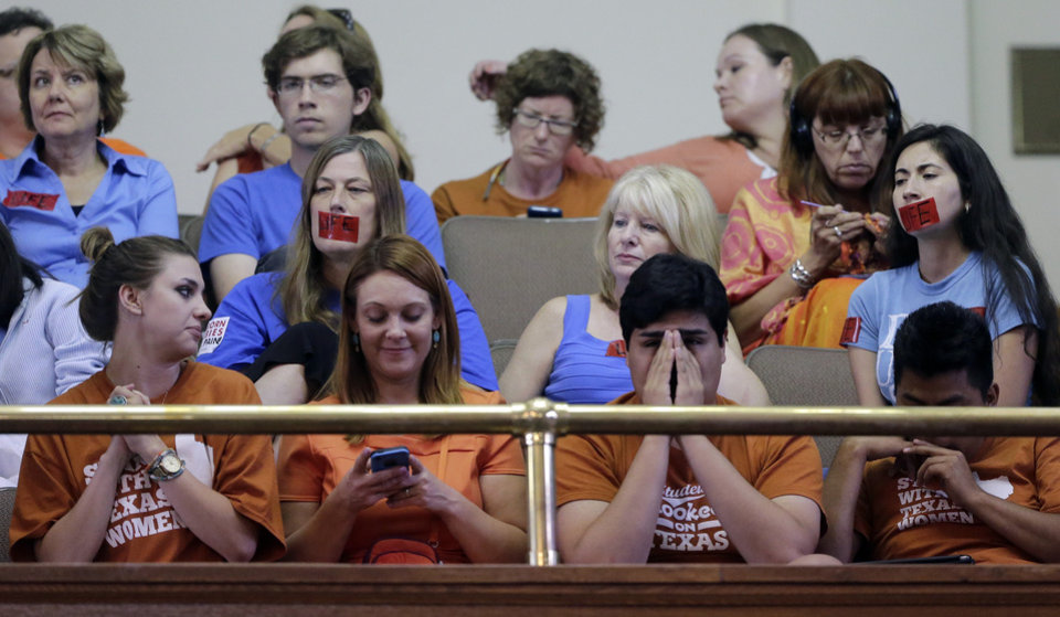 Supporters and opponents of an abortion bill, mostly dressed in blue or orange to show their side, sit in the gallery of the Texas Senate chambers as lawmakers debate before the final vote, Friday, July 12, 2013, in Austin, Texas. The bill would require doctors to have admitting privileges at nearby hospitals, only allow abortions in surgical centers, dictate when abortion pills are taken and ban abortions after 20 weeks. (AP Photo/Eric Gay)