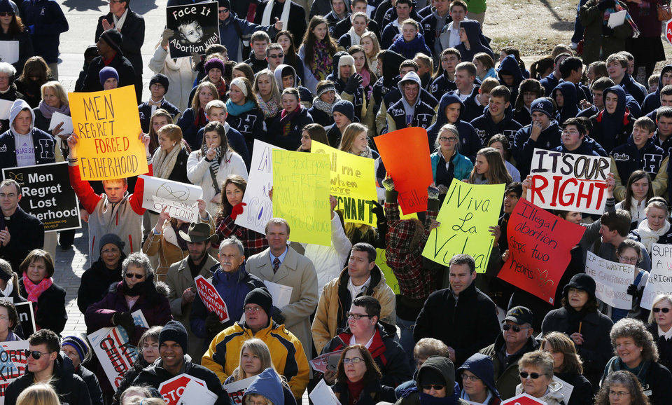 Abortion rights advocates hold signs during a Pro-Life rally on the steps of the Kansas Statehouse in Topeka, Kan., Tuesday, Jan. 22, 2013. Both sides met on the 40th anniversary of Roe v. Wade.  Gov. Sam Brownback has signed a series of tough, anti-abortion measures during his first two years in office. Much to the dismay of abortion-rights advocates, Kansas has been part of a wave in which states with Republican governors and GOP-controlled Legislatures enacted new restrictions on abortion providers.  (AP Photo/Orlin Wagner)