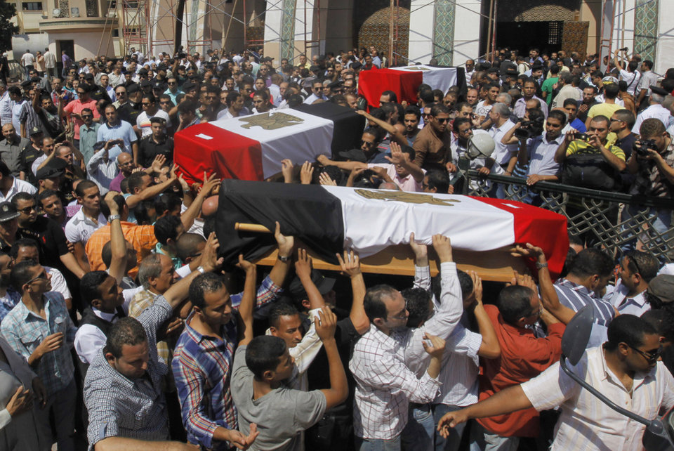 Photo - Egyptian relatives and colleagues of policemen who were killed during Wednesday's clashes carry coffins covered with national flags during a military funeral in Cairo, Egypt, Thursday, Aug. 15, 2013. Egyptian authorities on Thursday significantly raised the death toll from clashes the previous day between police and supporters of the ousted Islamist president, saying hundreds of people died and laying bare the extent of the violence that swept much of the country and prompted the government to declare a nationwide state of emergency and a nighttime curfew. (AP Photo/Amr Nabil)