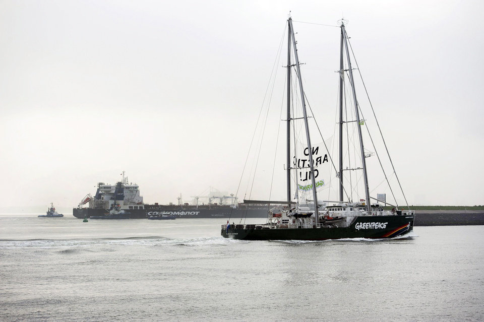 Photo - This image made available by environmental organization Greenpeace shows the Greenpeace ship Rainbow Warrior showing a banner reading: 'No Arctic Oil' as Greenpeace activists aboard inflatable boats paint 'No Arctic Oil' on the side of the Mikhail Ulyanov oil tanker, seen in the background, in Rotterdam, Netherlands, on Thursday, May 1, 2014. Greenpeace International activists are attempting to prevent a Russian tanker carrying the first oil from a new offshore platform in the Arctic from mooring at Rotterdam Port. The environmental group said Thursday it has sent two ships, Rainbow Warrior III and Esperanza, plus rubber rafts, paragliders and activists on shore, to meet the Mikhail Ulyanov, a tanker chartered by Russia's state-controlled oil company, Gazprom OAO. (AP Photo/Marten van Dijl, Greenpeace) NO SALES, NO ARCHIVE