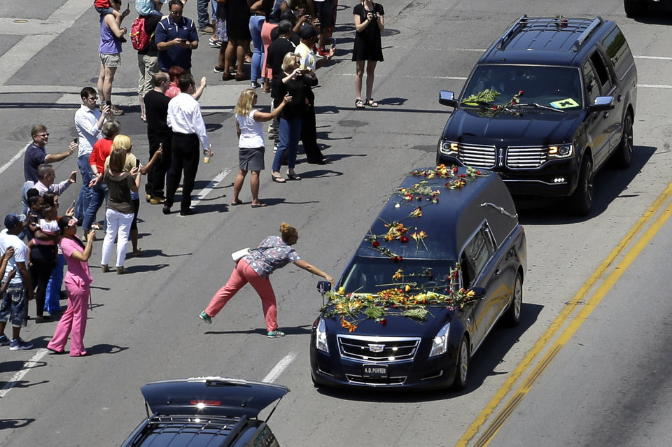 Photo - A woman reaches out to touch a hearse as Muhammad Ali's funeral procession passes onlookers lining the street Friday, June 10, 2016, in Louisville, Ky. (AP Photo/Jeff Roberson)