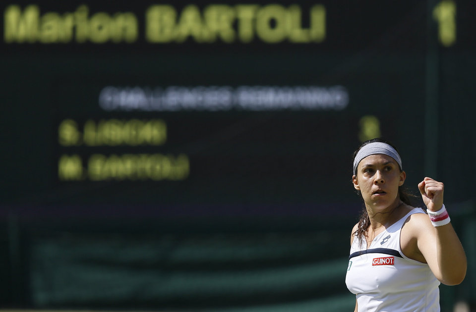 Photo - Marion Bartoli of France reacts after winning a point against Sabine Lisicki of Germany during their Women's singles final match at the All England Lawn Tennis Championships in Wimbledon, London, Saturday, July 6, 2013. (AP Photo/Kirsty Wigglesworth)