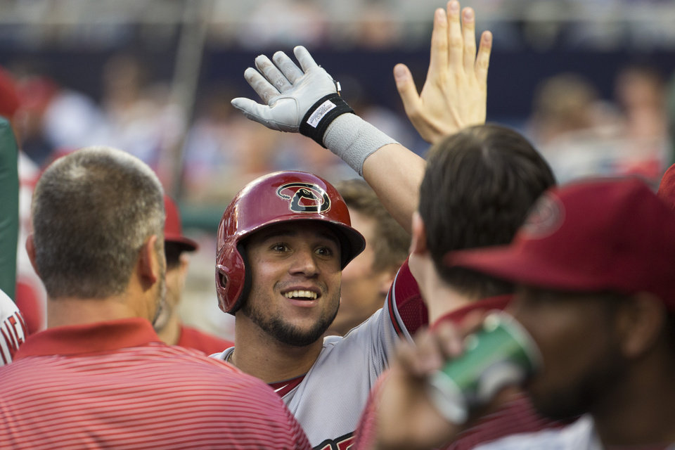 Photo - Arizona Diamondbacks' David Peralta smiles after hitting a home run during the first inning of a baseball game against the Washington Nationals on Tuesday, Aug. 19, 2014, in Washington. (AP Photo/Evan Vucci)