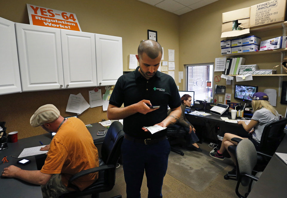 Photo - In this Aug. 25, 2014 photo, marijuana store  co-owner Kayvan Khalatbari, center, photographs a product label inside the front office of the marijuana shop Denver Relief, in Denver. Khalatbari also runs Denver Relief Consulting, which assists current and would-be marijuana-related businesses around the country, as well as owning a chain of pizza restaurants in Denver. (AP Photo/Brennan Linsley)
