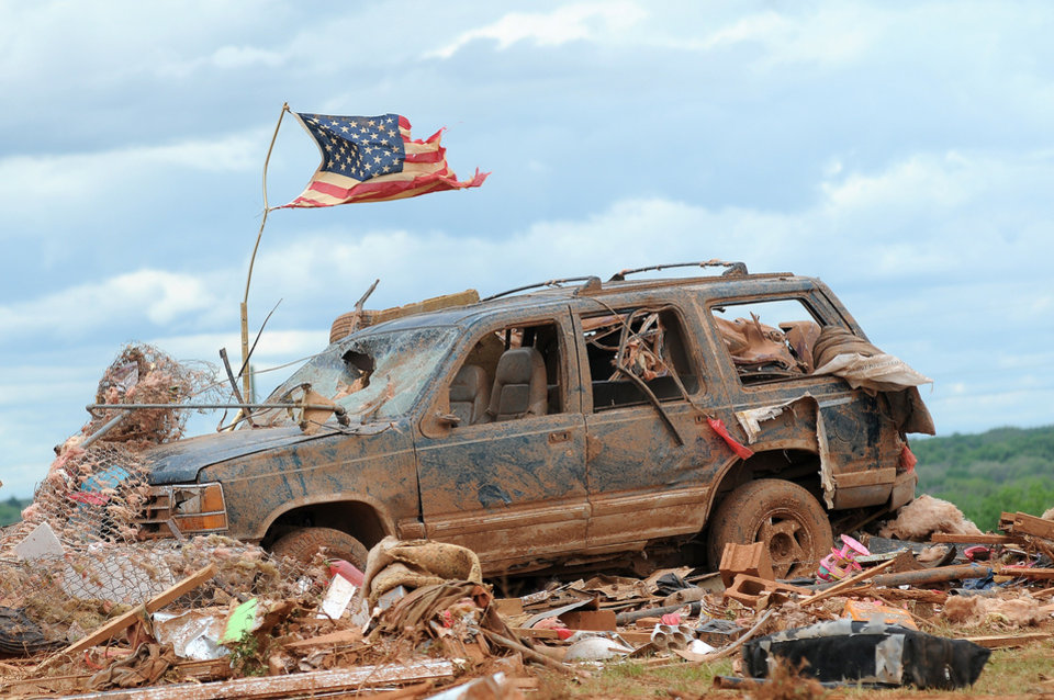 A tattered American flag flies over a vehicle where two young girls ages 5 and 7 were found after a severe thunderstorm spawned a massive tornado at Hideaway Mobile Home Villa in Woodward, Oklahoma shortly after midnight Sunday, April 15, 2012. The girls, Faith and Kelley Hobbie, ages 5 and 7, and their father, Frank Hobbie, were three of the five fatalities in the Northwest Oklahoma destruction. (AP Photo/ENID NEWS and EAGLE, BONNIE VCULEK)