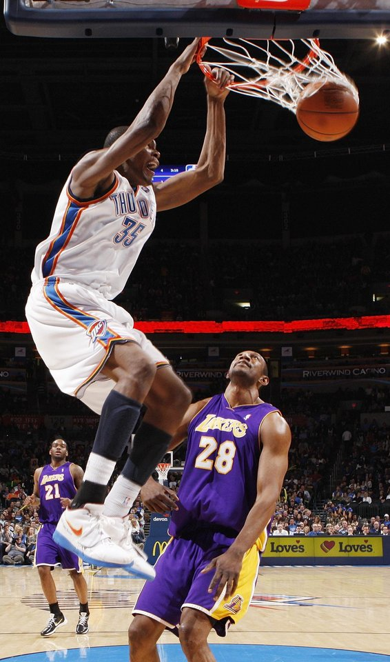 Photo - Kevin Durant (35) of Oklahoma City dunks the ball over DJ Mbenga (28) of Los Angeles in the fourth quarter during the NBA basketball game between the Los Angeles Lakers and the Oklahoma City Thunder at the Ford Center in Oklahoma City, Friday, March 26, 2010. Oklahoma City won, 91-75. Photo by Nate Billings, The Oklahoman