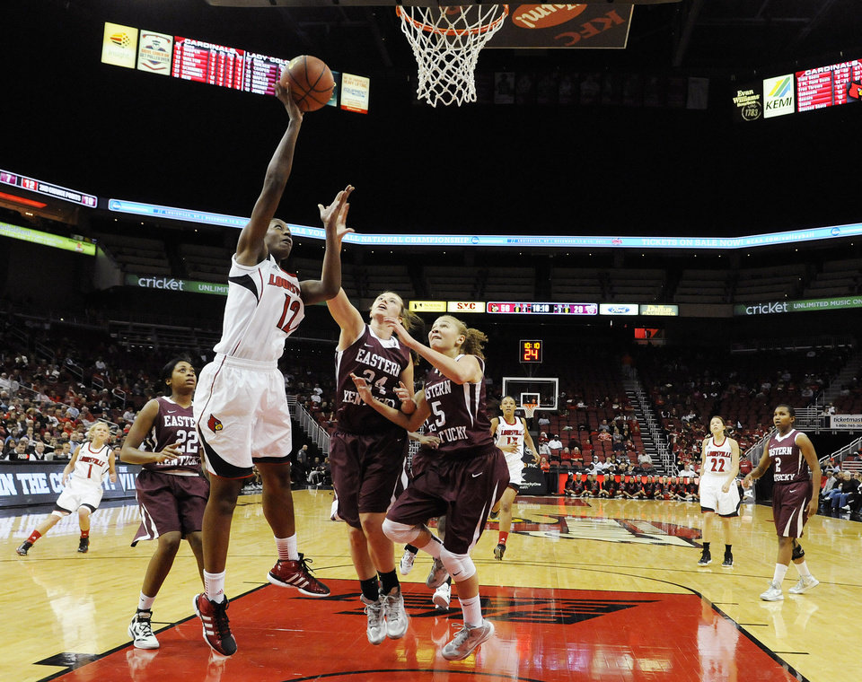 Photo -   Louisville's Shawnta Dyer, left, shoots against Eastern Kentucky's Miranda Maples, center, and Alexus Cooper during the second half of their NCAA college basketball game, Wednesday, Nov. 28, 2012, in Louisville, Ky. Louisville won 76-42. (AP Photo/Timothy D. Easley)