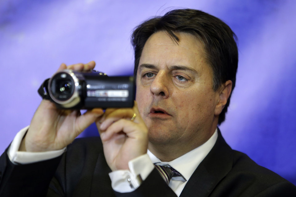 Photo - Leader of the far-right British National Party Nick Griffin uses his camera during a news conference in Athens on Friday, Jan. 10. 2014. Griffin, a member of the European Parliament, was in Athens to support Greece's extreme right Golden Dawn Party which is planning to challenge European Court of Human Rights against the recent arrest of the party's leadership on changes of criminal activity. (AP Photo/Thanassis Stavrakis)