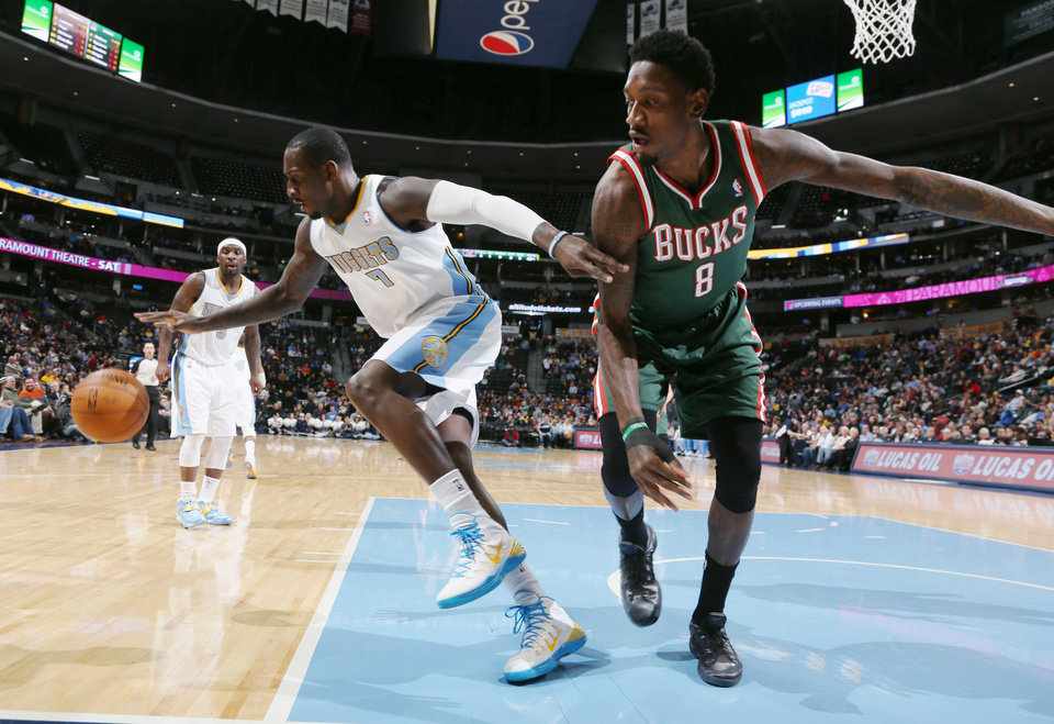 Photo - Denver Nuggets forward J.J. Hickson, left, scrambles after a loose ball with Milwaukee Bucks center Larryt Sanders in the first quarter of an NBA basketball game in Denver, Wednesday, Feb. 5, 2014. (AP Photo/David Zalubowski)