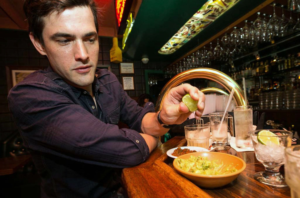 Photo - In this Monday, April 28, 2014 photo, Dana Stolzner squeezes lime juice to his guacamole, while drinking his own