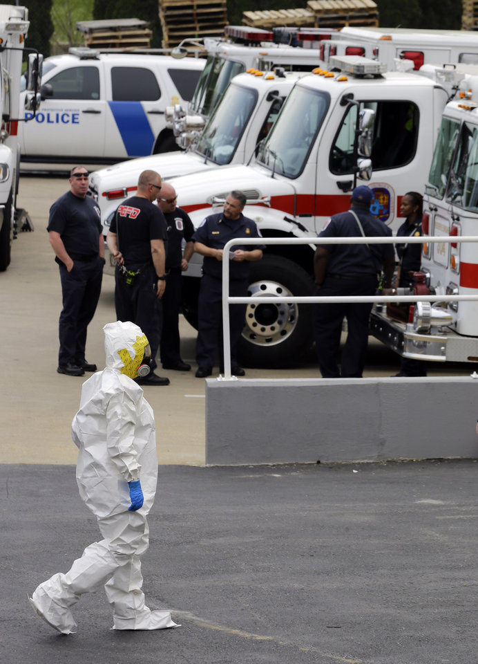 Photo - A Prince George's County, Md. firefighter dressed in a protective suit walks past emergency personell into a government mail screening facility in Hyattsville, Md., Wednesday, April 17, 2013. Police swept across the U.S. Capitol complex to chase a flurry of reports of suspicious packages and envelopes Wednesday after preliminary tests indicated poisonous ricin in two letters sent to President Barack Obama and a Mississippi senator.  (AP Photo/Alex Brandon)