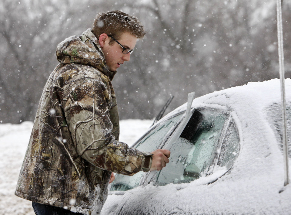 Photo - Michael Frazer clears the ice off of his car as he prepares to go to work in Edmond, OK, Friday, Jan. 29, 2010. By Paul Hellstern, The Oklahoman