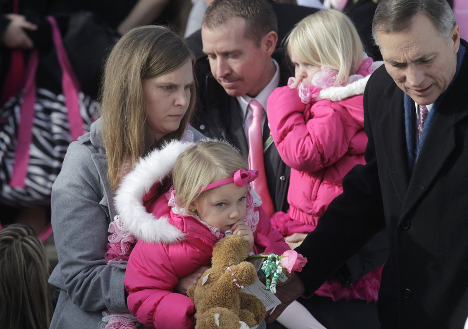 Photo - Alissa Parker, left, and her husband, Robbie Parker, center, carry their daughters, Samantha, 3, and Madeline, 4,  following funeral services for their 6-year old daughter,  Connecticut elementary shooting victim, Emilie Parker, Saturday, Dec. 22, 2012, at The Church of Jesus Christ of Latter-day Saints, in Ogden, Utah. Emilie, whose family has Ogden roots, was one of 20 children and six adult victims killed in on the Dec. 14 mass shooting at Sandy Hook Elementary in Newtown, Conn.  (AP Photo/Rick Bowmer)