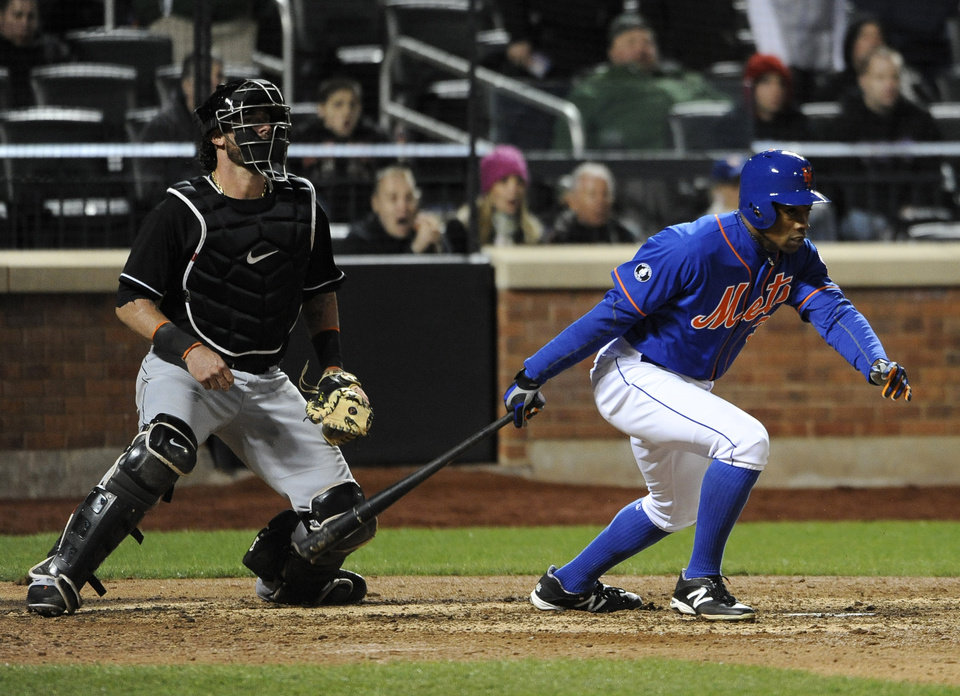Photo - Miami Marlins catcher Jarrod Saltalamacchia, left, watches New York Mets' Curtis Granderson (3) hit a walkoff single in the ninth inning to win a baseball game 4-3 at Citi Field on Friday, April 25, 2014, in New York. (AP Photo/Kathy Kmonicek)