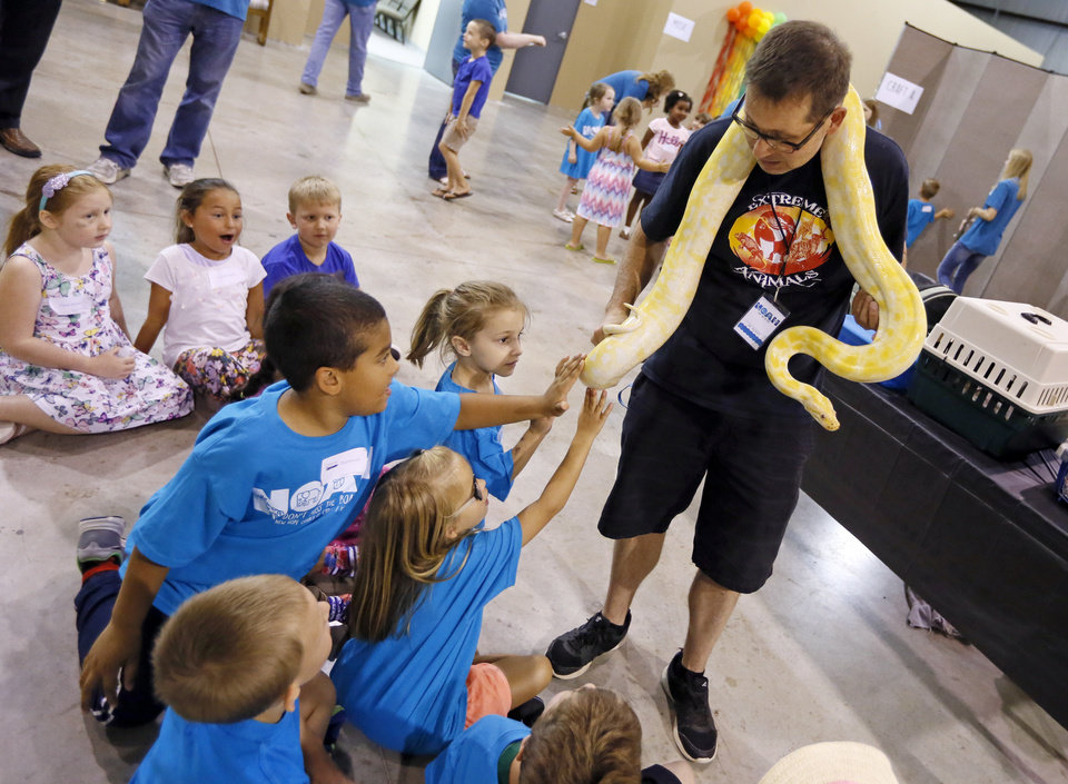 Photo -  Michael Seager, with Extreme Animals, shows children an albino Burmese python during vacation Bible school at Edmond's New Hope Church of Christ.  [PHOTOs BY NATE BILLINGS, THE OKLAHOMAN]