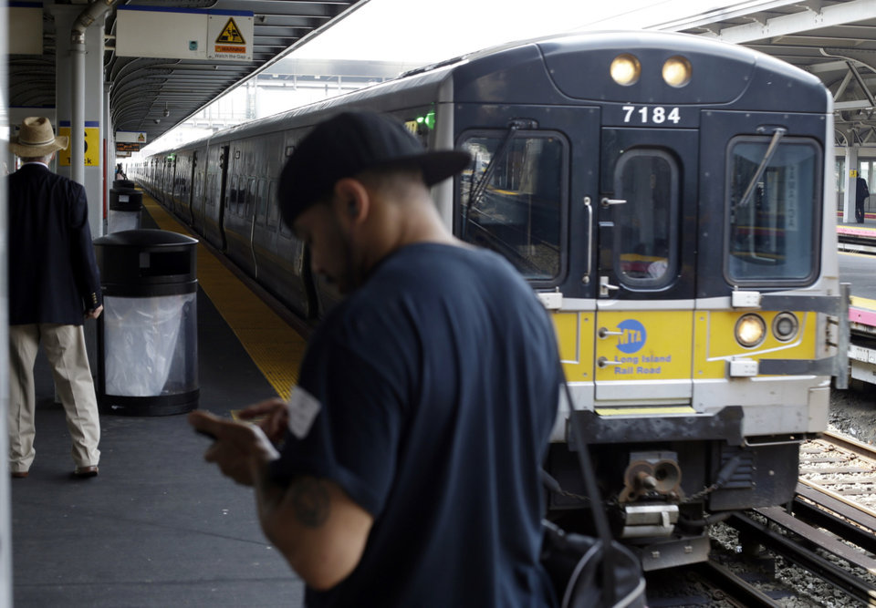 Photo - Pedestrians wait to ride a train at Jamaica station on the Long Island Rail Road Tuesday, July 15, 2014, in New York. Prospects of a strike which the unions said they were planning at 12:01 a.m. next Sunday, would affect 300,000 daily riders who travel in and out of New York City from Long Island. (AP Photo/Frank Franklin II)