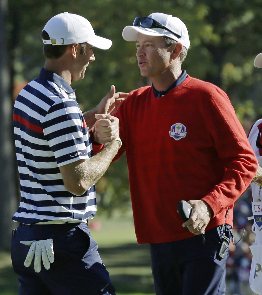 Photo - USA's captain Davis Love III congratulates Dustin Johnson after his singles match win over Europe's Nicolas Colsaerts at the Ryder Cup PGA golf tournament Sunday, Sept. 30, 2012, at the Medinah Country Club in Medinah, Ill. (AP Photo/David J. Phillip)  ORG XMIT: PGA164