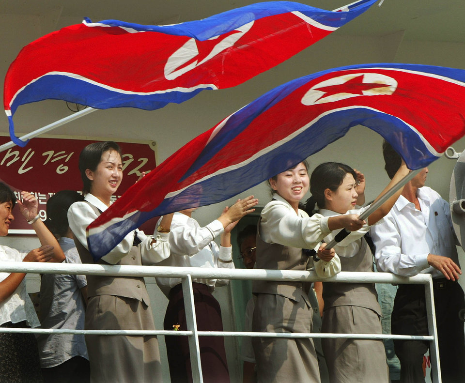 Photo - FILE - In this Monday, Aug. 25, 2003 file photo, North Korean woman crew wave the national flags aboard North Korean ferry Mangyongbong-92 on its arrival at the northern Japanese port of Niigata, Japan. Until the Mangyongbong-92 was banned in 2006, Wonsan was a bustling port of entry for Japanese capital. The ferry was a crucial means for the ethnic Koreans in Japan to visit the North, often laden with gifts, supplies and cash for their relatives or friends, bringing a wide variety of products not normally available in the socialist state. In its peak years, the Mangyongbong-92 was believed to have transported hundreds of millions of dollars worth of goods and cash to the North. (AP Photo/Itsuo Inouye, File)
