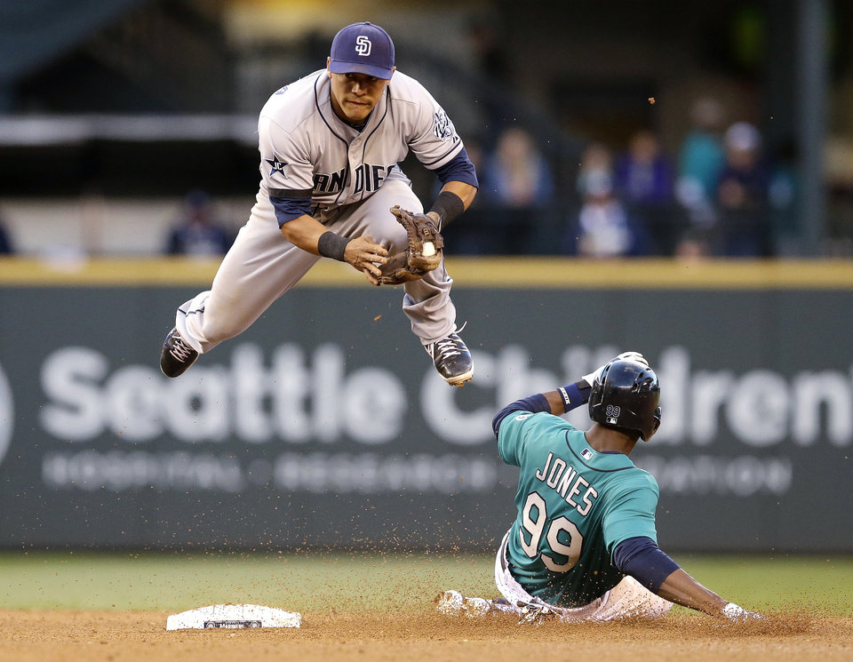 Photo - San Diego Padres second baseman Alexi Amarista leaps to get out of the way of sliding Seattle Mariners' James Jones (99) at second base in the fourth inning in a baseball game Monday, June 16, 2014, in Seattle. Jones was forced out, but Robinson Cano was safe at first base on a fielder's choice. (AP Photo/Elaine Thompson)